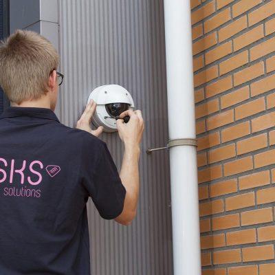 Een afbeelding van een sfeerbeeld op gks.nl waarop een man een bewakingscamera op een pand installeert.