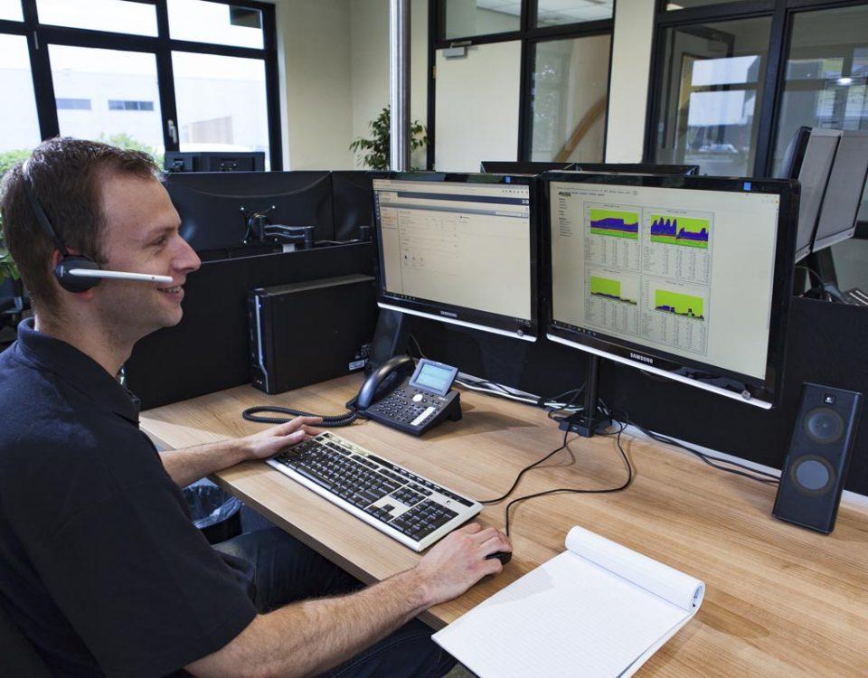 Een GKS medewerker levert telefonisch support en ziet grafieken op zijn beeldscherm
